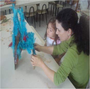 Professora ajudando a adereçar escultura